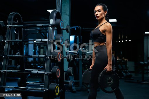 istock Woman holding weights near barbells. 1264091184