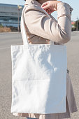 Woman holding white canvas bag