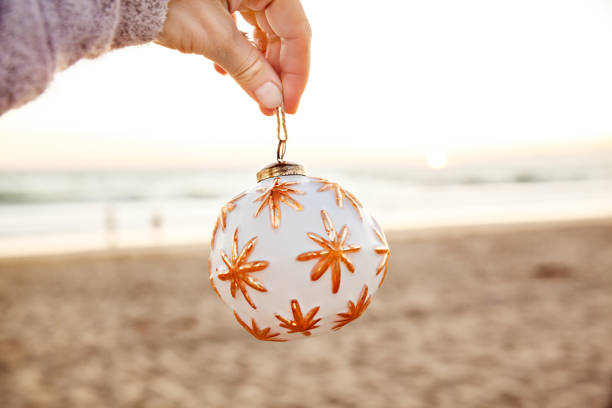 Woman holding white Christmas ball on the beach at sunset in California stock photo