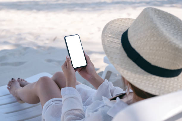 a woman holding white mobile phone with blank desktop screen while laying down on beach chair on the beach - phone, travelling, copy space imagens e fotografias de stock