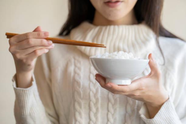 白いご飯と箸をボウルに入れておる女性 - ご飯茶碗 ストックフォトと画像