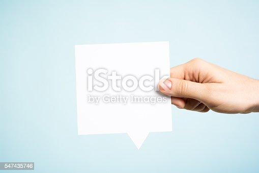 istock Woman holding white square blank speech bubble, blue background 547435746