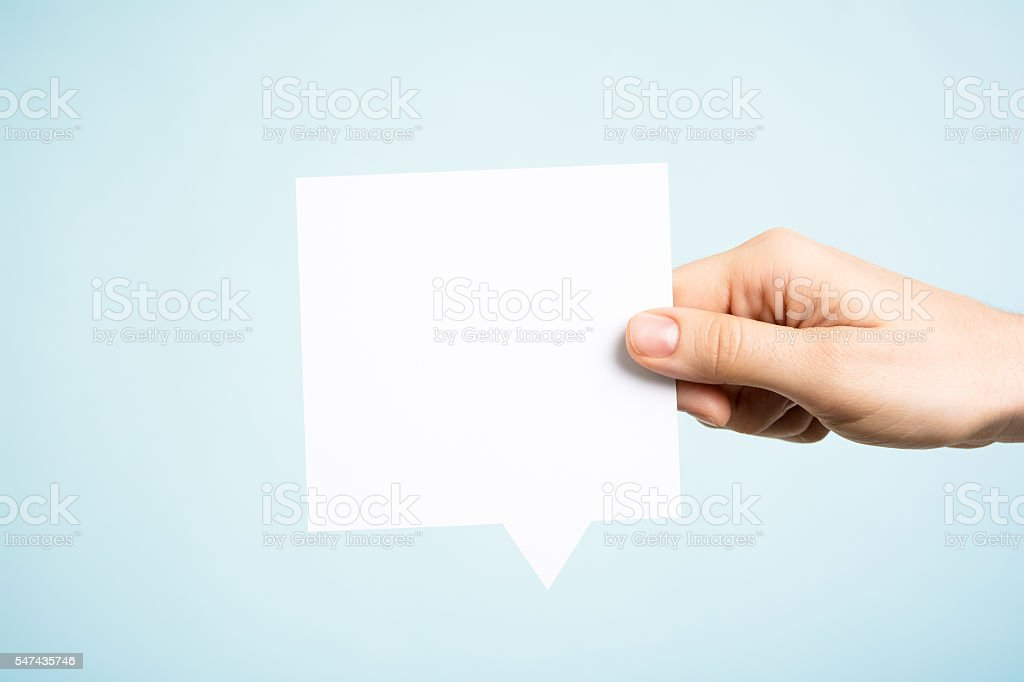 Woman holding white square blank speech bubble, blue background stock photo