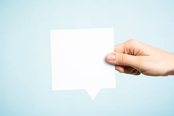 Woman holding white square blank speech bubble, blue background 스톡 사진