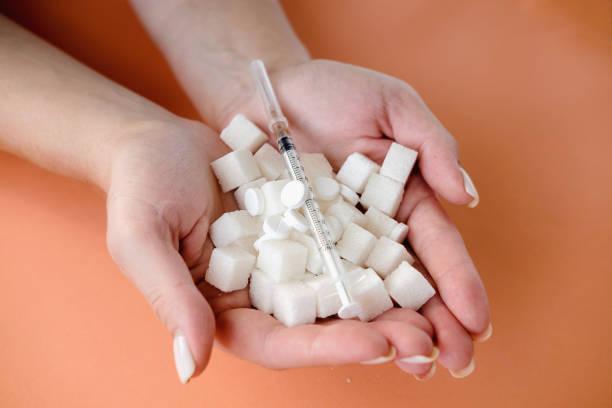 frau hält weiße zuckerwürfel und insulinspritze auf orangen hintergrund. diabetes, zuckerkrankheit, ungesunde ernährung, ernährungskonzept. kopierraum - dextrose stock-fotos und bilder