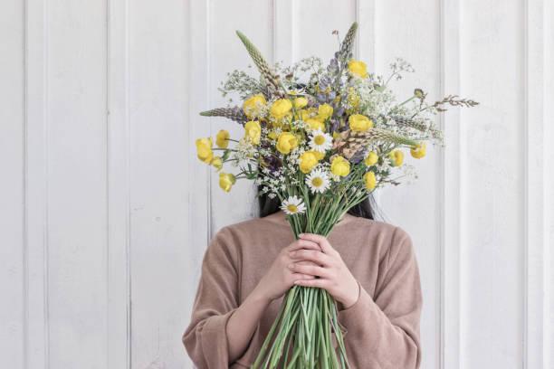 Frau hält wilden gelben Blumenstrauß – Foto