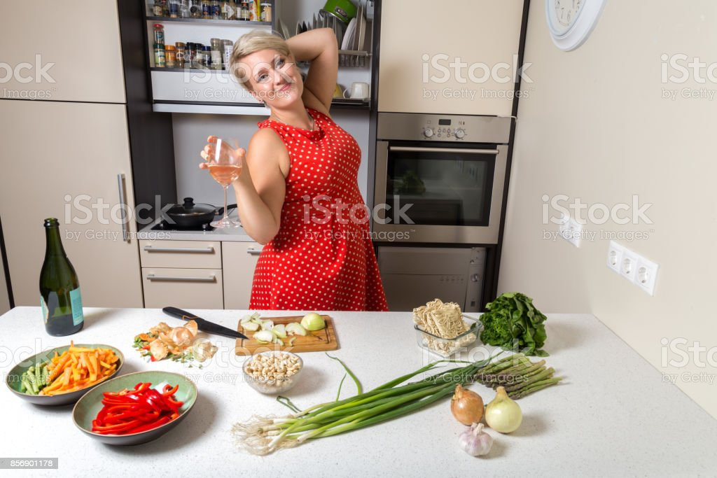 Woman holding wine glass in kitchen stock photo