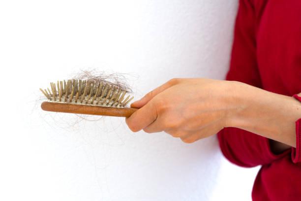 Frau hält hölzerne Haarbürste voll von Haaren, die herausgefallen ist – Foto