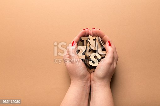 istock Woman holding wooden letters on beige background 935412080