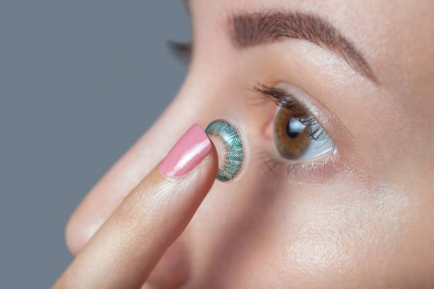 woman holds a blue contact lens on her finger. - contacts imagens e fotografias de stock