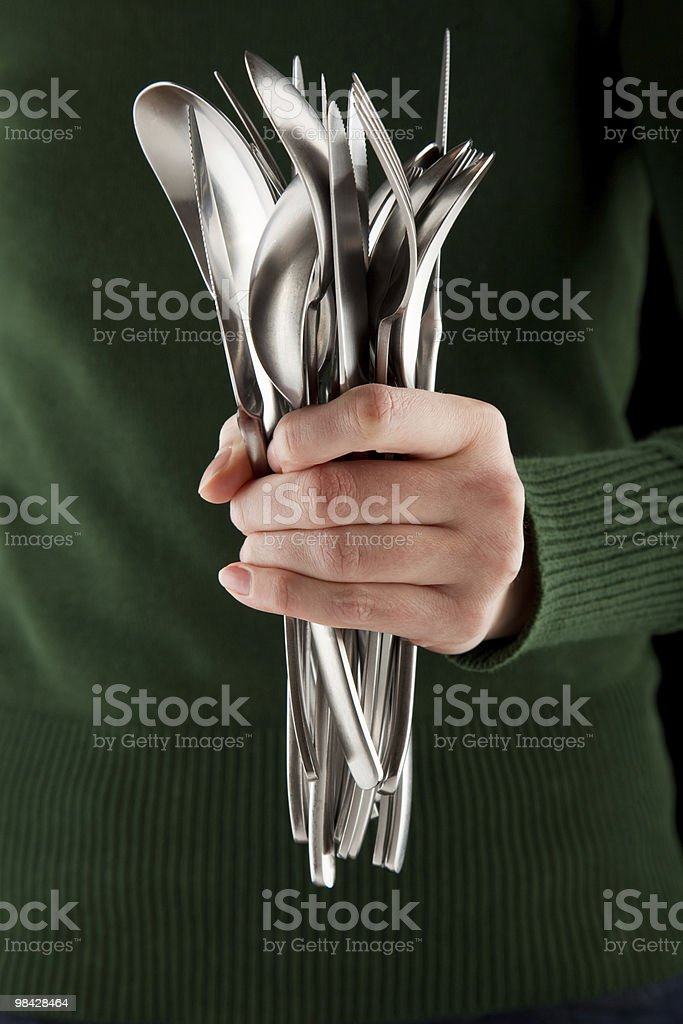 woman holds a bunch of silverware in her hand royalty-free stock photo