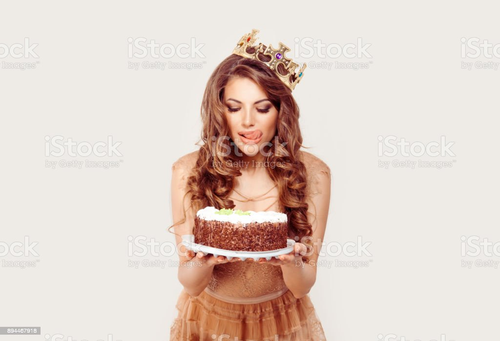 Woman holds a cake in her hands craving to eat it licking her lips, she can not help but keep it isolated white background. Girl full makeup curly brown long hair blue eyes beige skin tone lace dress stock photo