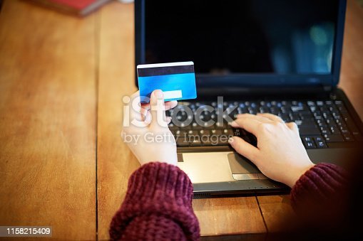 Young woman pays for goods online with her credit card and laptop computer.