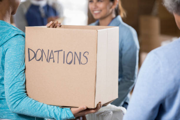 Woman holds a donation box during food and clothing drive stock photo
