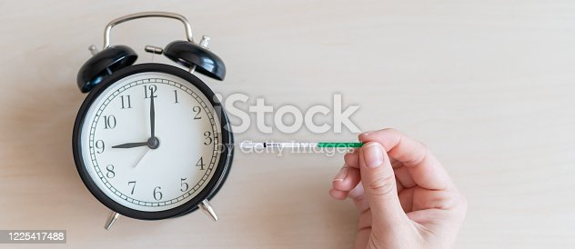 Woman holds a positive pregnancy test and alarm clock. Nine months of pregnancy. The concept of the biological clock of fertility