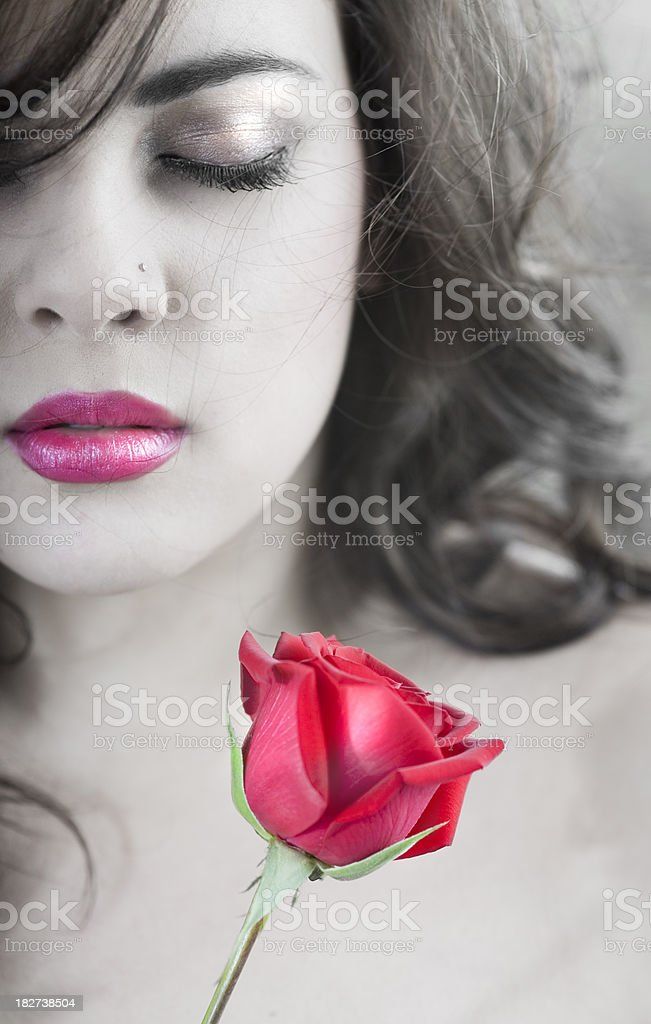 Woman Holds a Rose against Pale Body stock photo