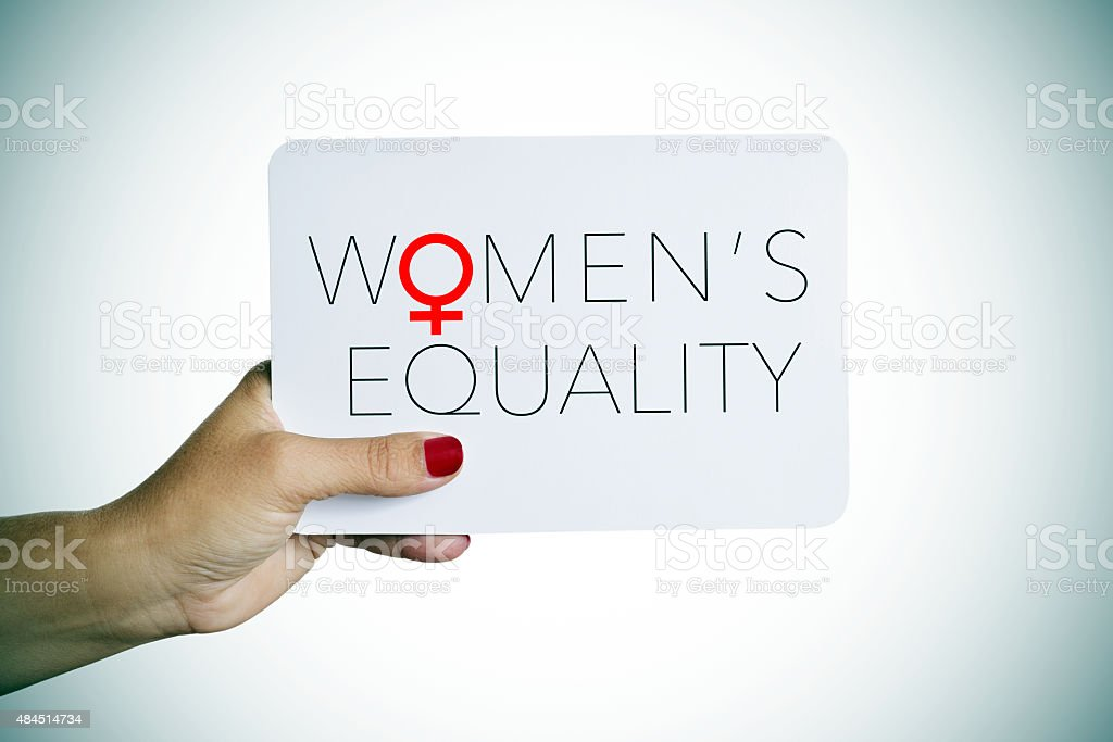 woman holds a signboard with the text womens equality stock photo