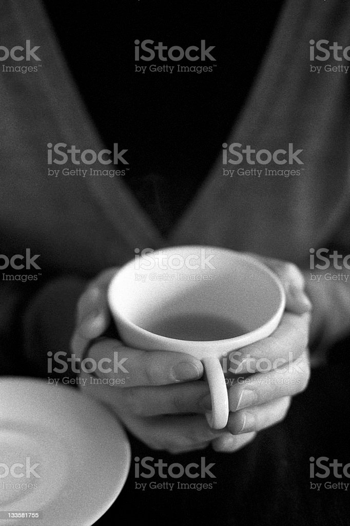Woman holds a warm cup of tea in her hands Two female hands holding a half-empty cup of tea. Shallow depth of focus, film grain visible (scan from Delta 3200). Also see: Adult Stock Photo