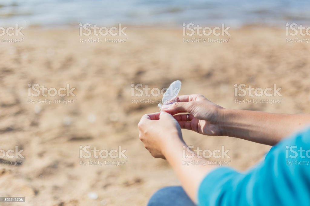 Woman holds a white feather of a seagull in hand. Symbol of lightness and fragility. stock photo