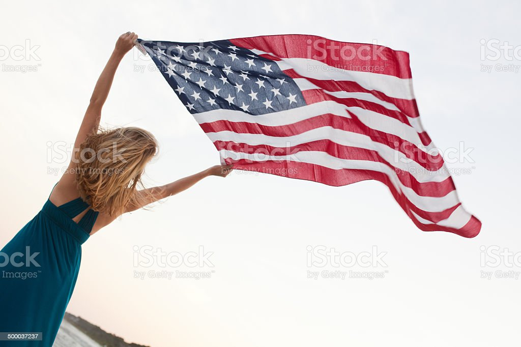 Woman holds American flag over her head stock photo