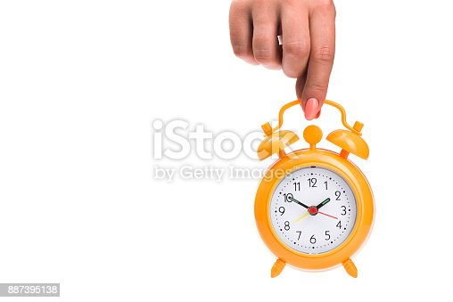 woman holds an alarm clock in her hands isolated on white background, time to breakfast or relax