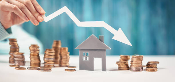 Woman holds an arrow down over model of the house and stack of coins. stock photo