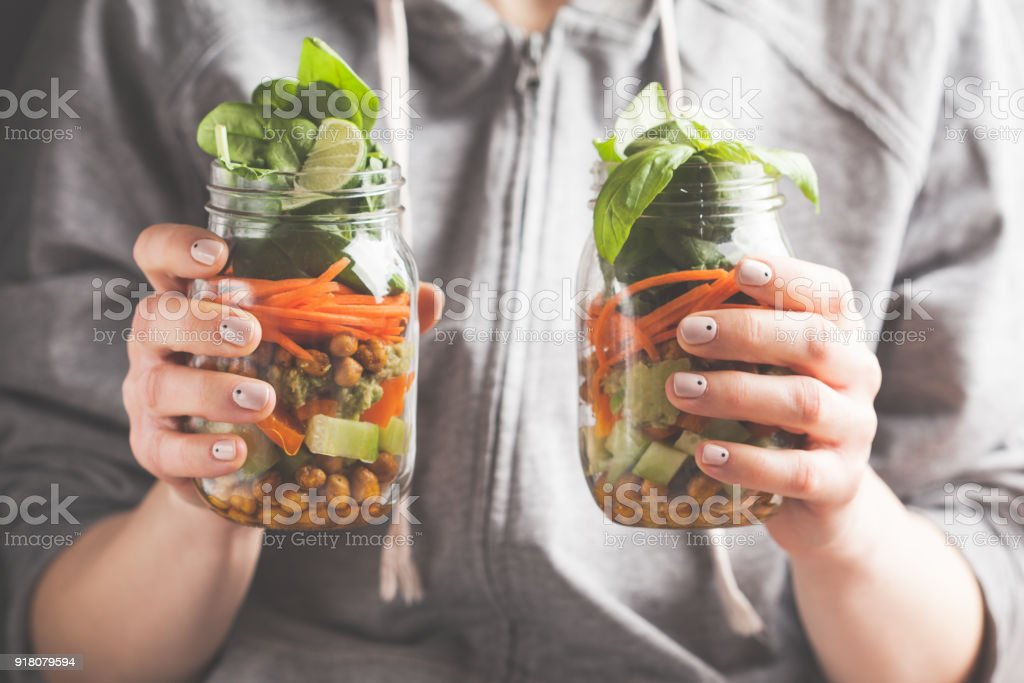A woman holds and eats a salad in a glass jar with baked chickpeas, guacamole and vegetables. Healthy diet detox vegan food concept. stock photo