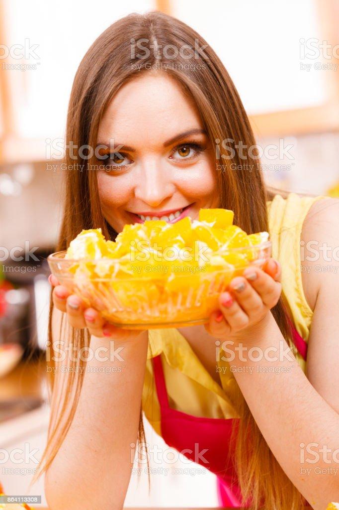 Woman holds bowl full of sliced orange fruits royalty-free stock photo