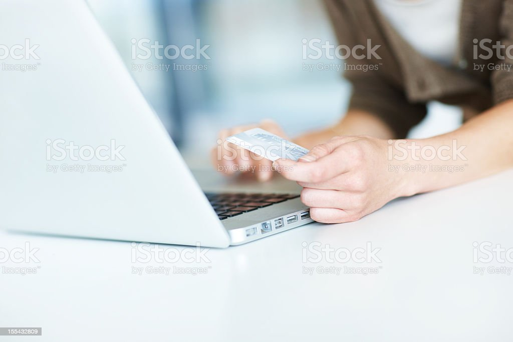 Woman holds credit card above laptop keyboard royalty-free stock photo