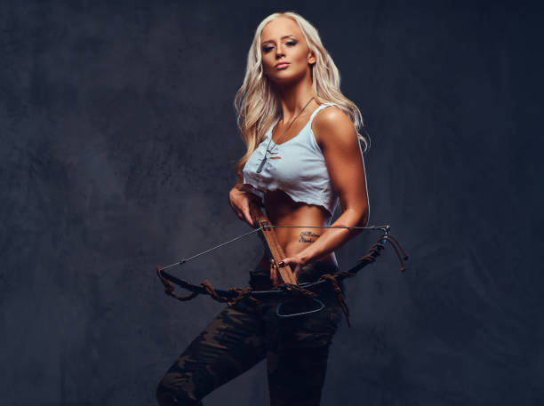 a woman holds crossbow. - crossbow stock pictures, royalty-free photos & images