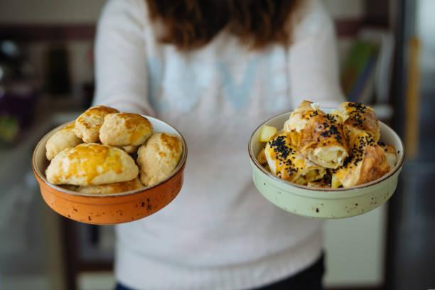 frau hält gefüllte gebäck in schüssel und türkischen patty, börek - spieltag vorspeisen stock-fotos und bilder
