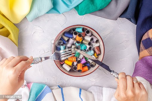 Woman holds fork and knife under the bowl with spools of thread in fabric multi-colored frame on grey background
