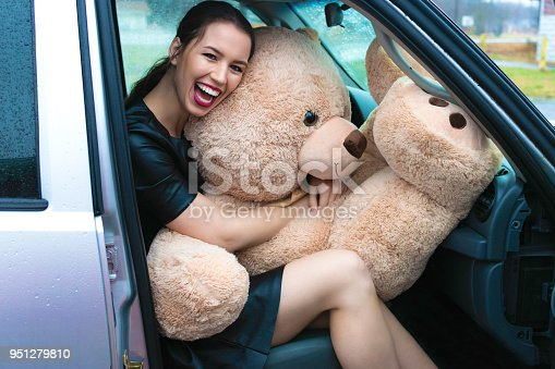 A beautiful woman in bright lipstick looks at camera and holds oversized teddybear in the passenger seat of car.