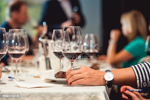 istock woman holds glass of red wine. people consider the color of the wine and try how it smells in different glasses 936470018
