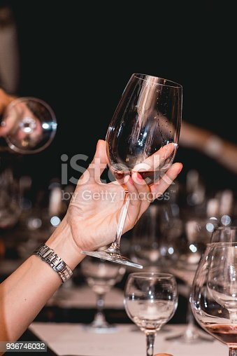 istock woman holds glass of red wine. people consider the color of the wine and try how it smells in different glasses 936746032