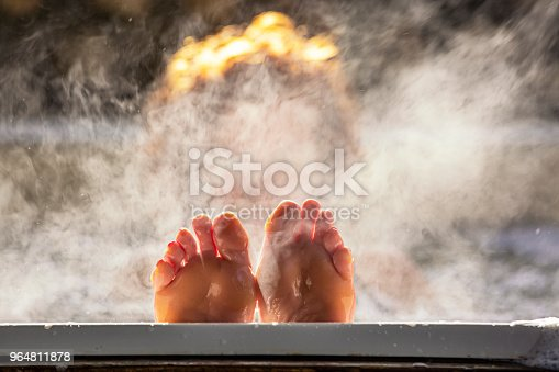 Woman holds her feet up while in a hot tub with steam
