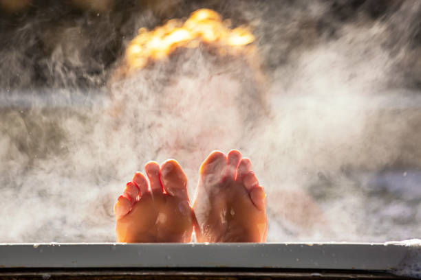 Woman holds her feet up while in a hot tub Woman holds her feet up while in a hot tub with steam bathtub stock pictures, royalty-free photos & images