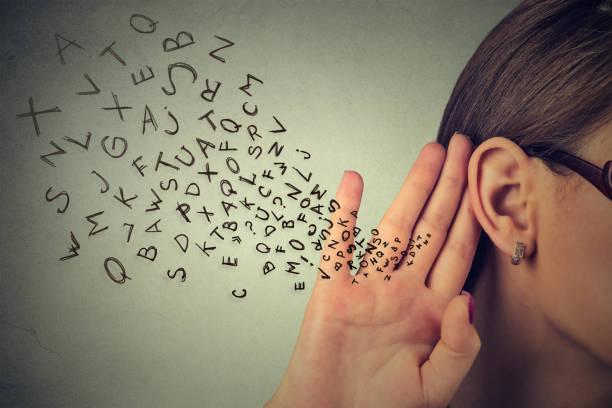 Mujer sostiene su mano junto a la oreja y escucha atentamente - foto de stock