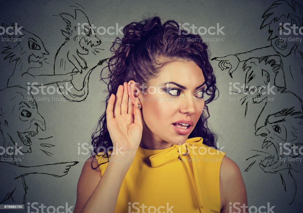 woman holds her hand near ear and listens carefully to evil voices royalty-free stock photo