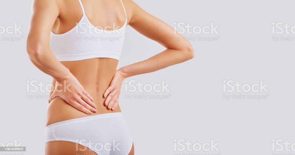 A woman holds her hand with a painful back. stock photo