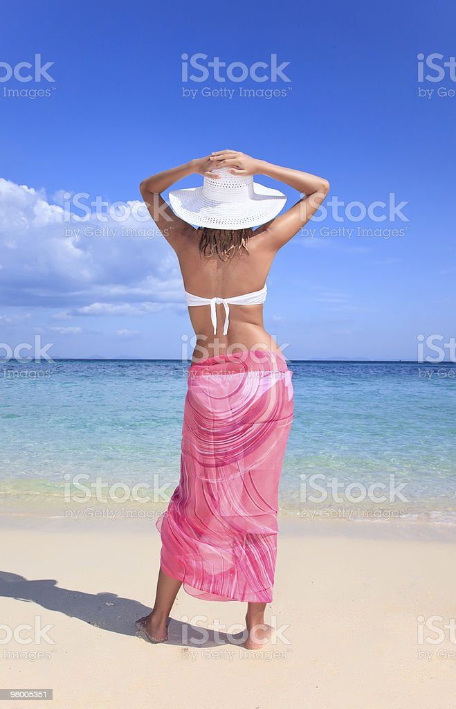 woman holds her hat down standing on beach royalty-free stock photo