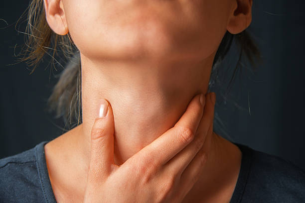 Woman holds her throat, sore throat stock photo