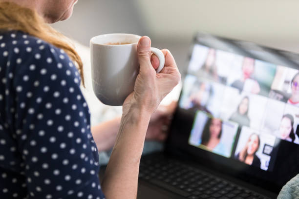 Woman holds hot cup of coffee while video conferencing stock photo