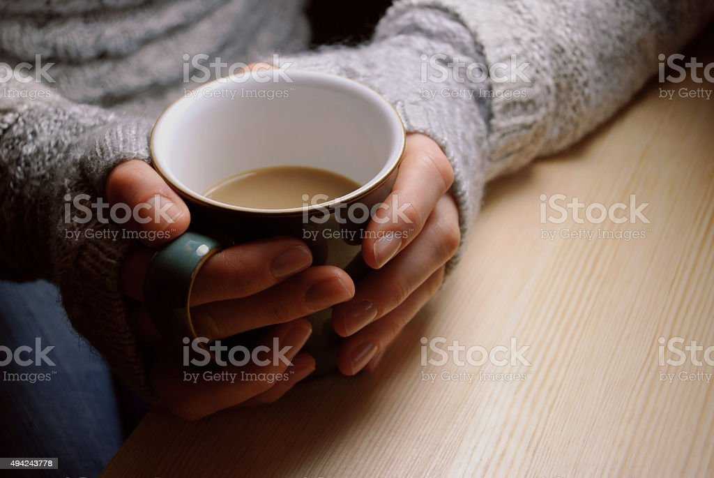 Woman holds hot drink at a table under lamplight stock photo