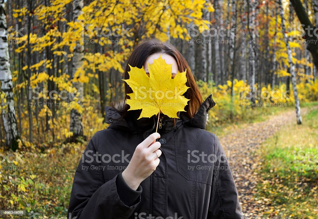 Woman holds huge yellow maple leaf in the hand royalty-free stock photo