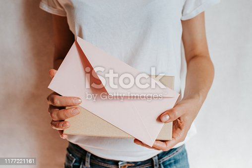 istock Woman holds in hand paper envelope and box. New mail, message. Postal service. Young girl want send or receive letter and package. Blank envelope, empty space. People communication. Envelope closeup 1177221161