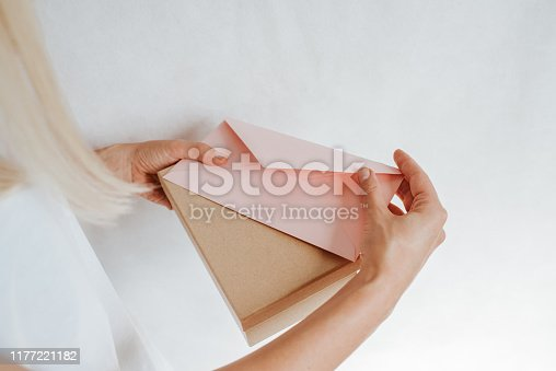 istock Woman holds in hand paper envelope and box. New mail, message. Postal service. Young girl want send or receive letter and package. Blank envelope, empty space. People communication. Envelope closeup 1177221182