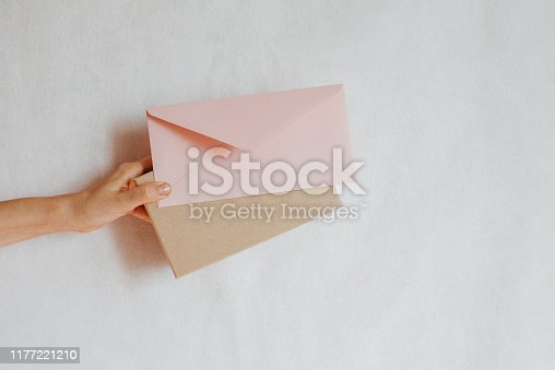 istock Woman holds in hand paper envelope and box. New mail, message. Postal service. Young girl want send or receive letter and package. Blank envelope, empty space. People communication. Envelope closeup 1177221210