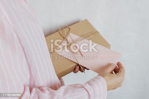 istock Woman holds in hand paper envelope and box. New mail, message. Postal service. Young girl want send or receive letter and package. Blank envelope, empty space. People communication. Envelope closeup 1179206269