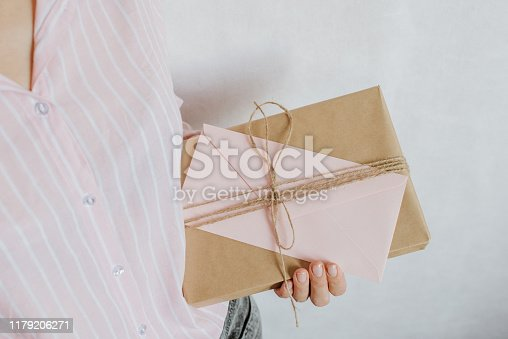 istock Woman holds in hand paper envelope and box. New mail, message. Postal service. Young girl want send or receive letter and package. Blank envelope, empty space. People communication. Envelope closeup 1179206271